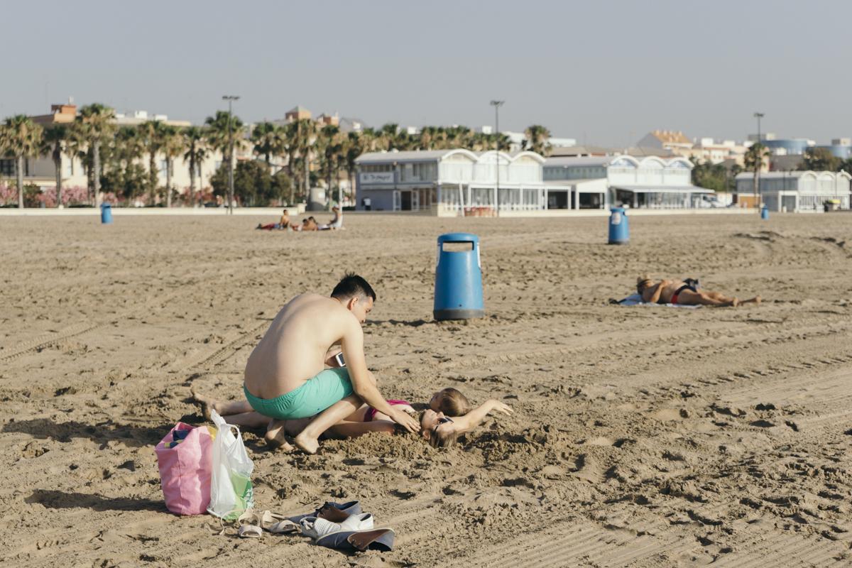 Man, sand-burying his family
